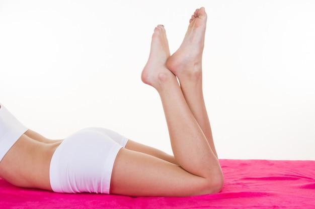 Conceito de saúde e beleza long woman legs deitado na toalha rosa isolada no branco
