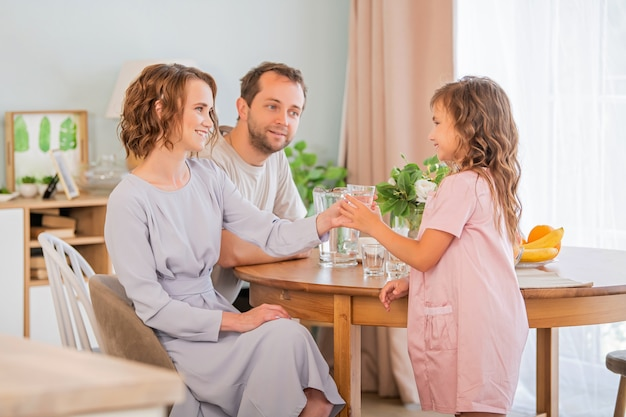 Conceito de saúde e beleza - mãe sorridente dá um copo de água para sua filha. pai feliz em segundo plano.