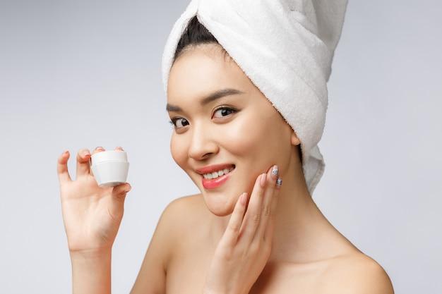 Conceito de saúde e beleza - mulher asiática atraente aplicando creme na pele, isolado no branco.