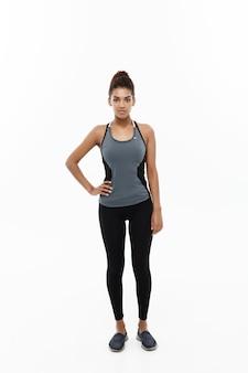 Conceito de saúde e fitness - retrato de uma garota afro-americana, posando com roupas de ginástica isoladas em branco.