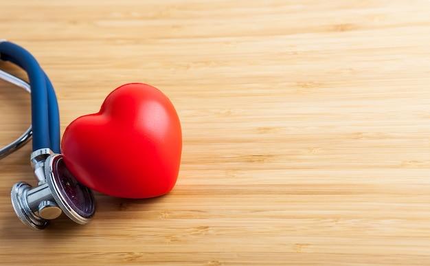 Conceito de saúde e médico. estetoscópio e coração vermelho na mesa de madeira.