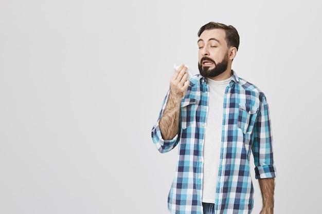 Conceito de saúde. homem doente com alergia, espirrando em guardanapo