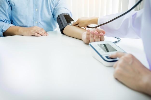 Conceito de saúde, hospital e medicina - médico e paciente que medem a pressão arterial.