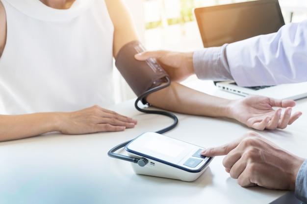 Conceito de saúde, hospital e medicina - médico e paciente que medem a pressão arterial