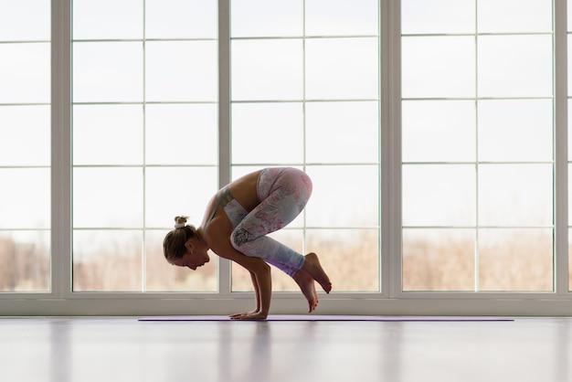 Conceito de saúde. jovem e bela mulher fazendo exercícios de ioga em um quarto moderno