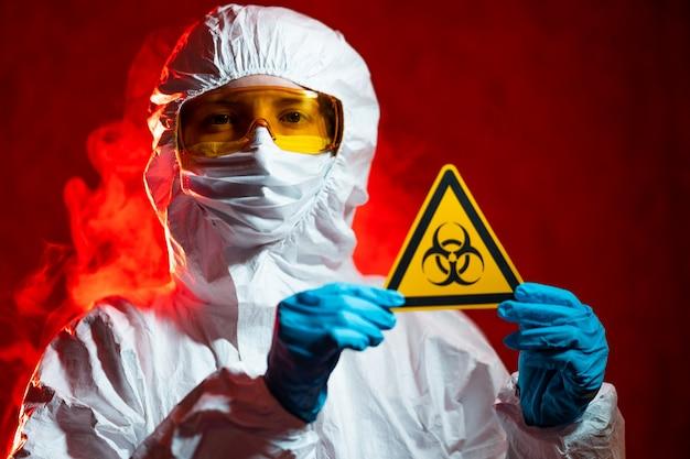 Conceito de saúde, medicina e pandemia - médico feminino segurando o sinal de advertência boihazard
