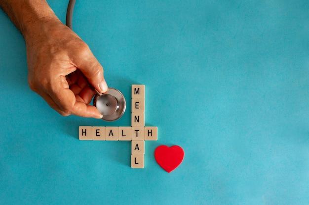 Conceito de saúde mental com telhas de carta e estetoscópio sobre fundo azul. copie o espaço.