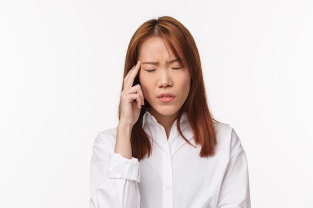 Conceito de saúde, midicine e pessoas. o retrato do close-up da mulher asiática nova cansada e tonta que sofre de dor de cabeça, fecha os olhos e toca o templo, faz uma careta de sentimento doloroso, tem enxaqueca,