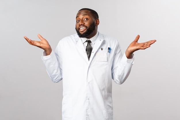 Conceito de saúde. não sei, não posso ajudar, desculpe. retrato de médico afro-americano bonito, relutante e despreocupado, encolher os ombros à nora, intrigado e sem ideia