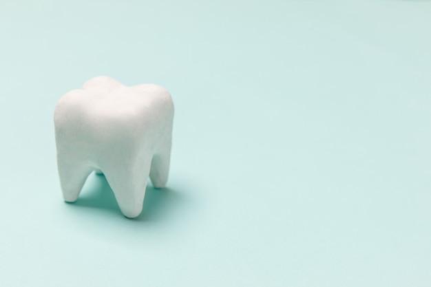 Conceito de saúde odontológica. modelo de dente branco saudável isolado em pastel