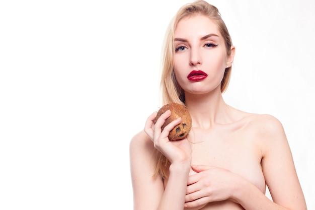 Conceito de saúde, pessoas, alimentação e beleza - linda garota com uma maquiagem leve e natural e pele perfeita com coco na mão