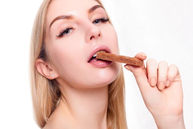 Conceito de saúde, pessoas, comida e beleza - adorável adolescente sorridente comendo chocolate. retrato de mulher bonita segurando a barra de chocolate.