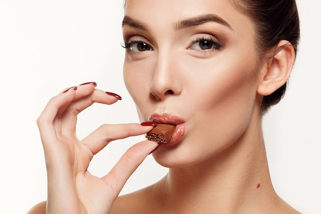 Conceito de saúde, pessoas, comida e beleza - adorável adolescente sorridente comendo chocolate