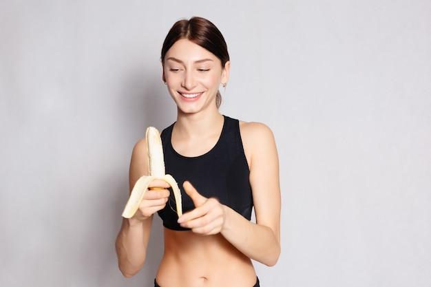 Conceito de saúde, pessoas, comida, esporte e beleza - jovem desportiva segurando um cacho de bananas. alimentação e dieta saudáveis. o conceito de nutrição adequada. cuidado do corpo. em um fundo cinza
