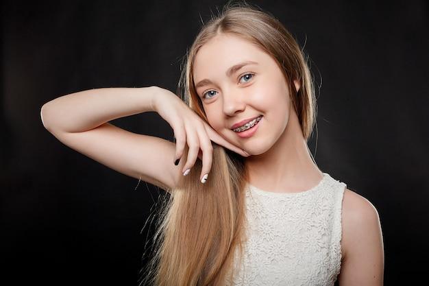Conceito de saúde, pessoas, juventude, odontologia e beleza - retrato de uma adolescente mostrando o aparelho dentário.