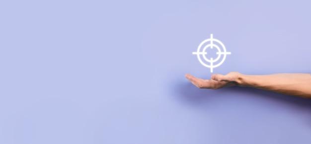 Conceito de segmentação com a mão do empresário segurando o esboço do ícone do alvo para dardos na lousa. alvo objetivo e conceito de meta de investimento.