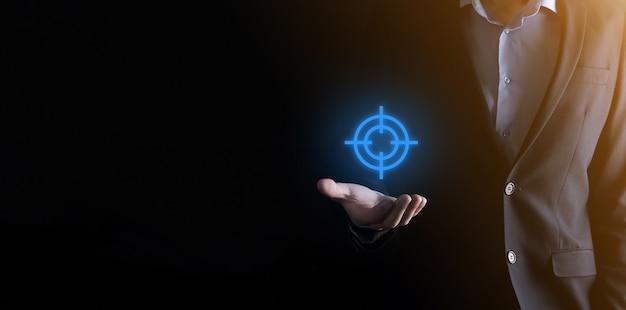 Conceito de segmentação com mão de empresário segurando o esboço do ícone do alvo para dardos na lousa
