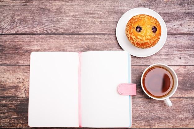 Conceito de segunda de manhã, chá quente e bolo de muffin no espaço de trabalho de madeira