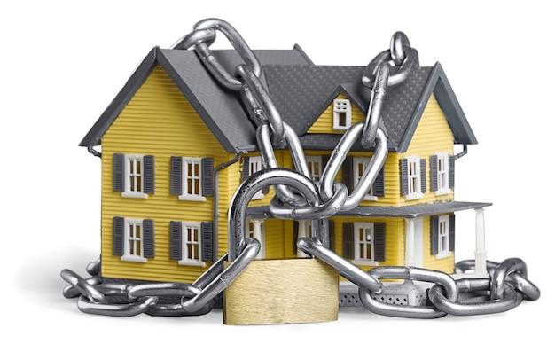 Conceito de segurança da casa. casa acorrentada isolada no branco