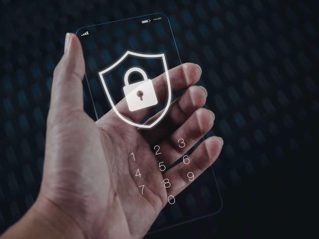 Conceito de segurança e privacidade do smartphone. gráfico de ícone de escudo e bloqueio branco com números para senha na tela de bloqueio do telefone de vidro transparente futurista muito fino na mão em fundo de tom escuro.