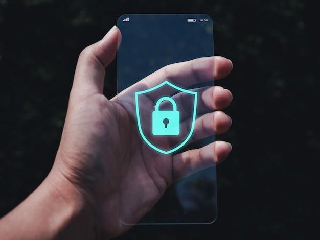 Conceito de segurança e privacidade do smartphone. gráfico de ícone de escudo e cadeado azul na tela do telefone de vidro transparente futurista muito fino na mão em fundo de tom escuro.
