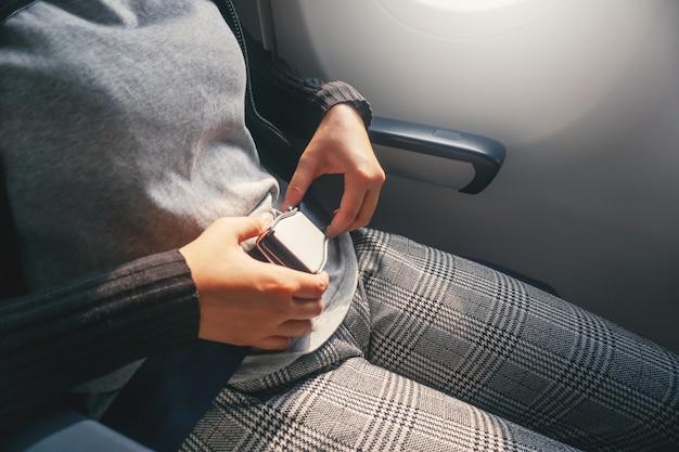 Conceito de segurança mulher asiática é cinto de fixação no avião pronto para decolar