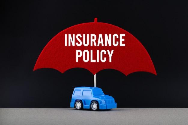 Conceito de seguro automóvel. carro azul sob o guarda-chuva vermelho com apólice de seguro de texto.