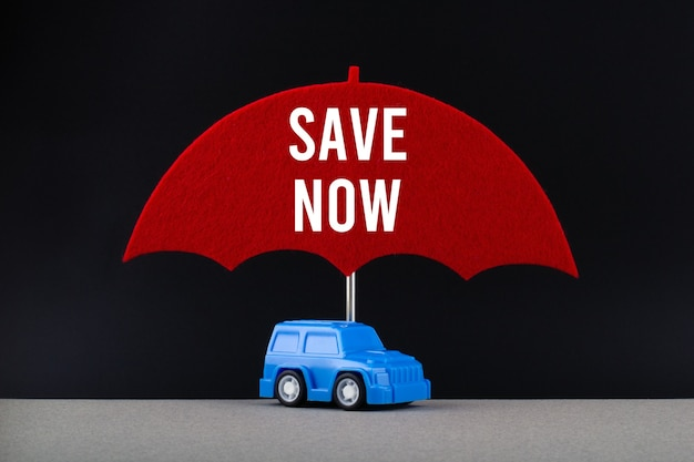 Conceito de seguro automóvel. carro azul sob o guarda-chuva vermelho com o texto salvar agora.