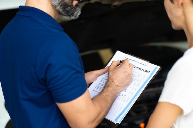 Conceito de seguro automóvel. o agente de seguros examina o carro danificado com as informações escritas do cliente no formulário de relatório de sinistro.
