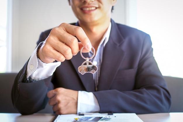 Conceito de seguro de aluguel de carro e jovem vendedor sentado na mesa pronta para entregar as chaves do carro aos clientes após a assinatura do contrato com um bom contrato de locação ou compra.