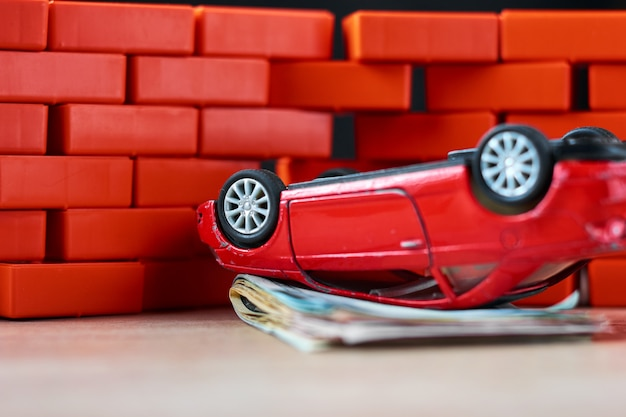 Conceito de seguro de carro. carro quebrado e uma pilha de notas de dólares