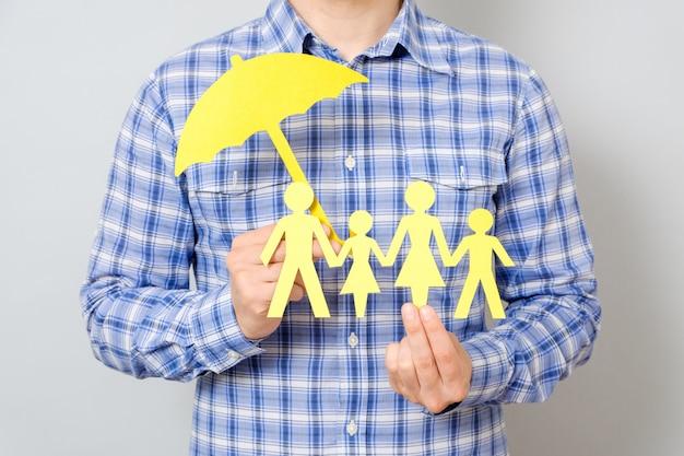 Conceito de seguro de família com guarda-chuva para proteger uma família
