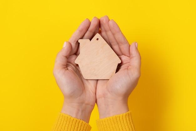 Conceito de seguro de propriedade com brinquedo de casa nas mãos sobre fundo amarelo