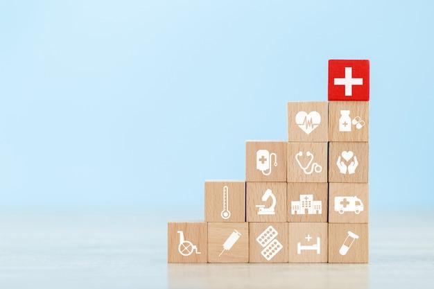Conceito de seguro de saúde. bloco de madeira que empilha com os cuidados de saúde do ícone médicos.