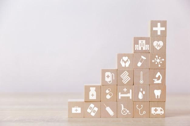 Conceito de seguro de saúde, mão organizando o empilhamento de bloco de madeira com cuidados de saúde de ícone médica, para a saúde