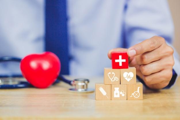 Conceito de seguro de saúde, mão organizando o empilhamento de bloco de madeira com médicos de cuidados de saúde de ícone