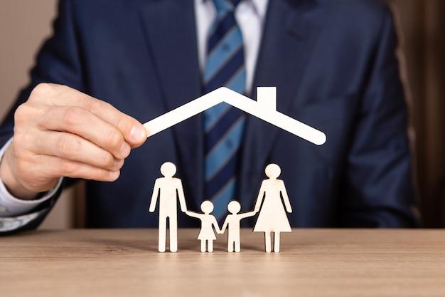 Conceito de seguro familiar com as mãos protegendo uma família
