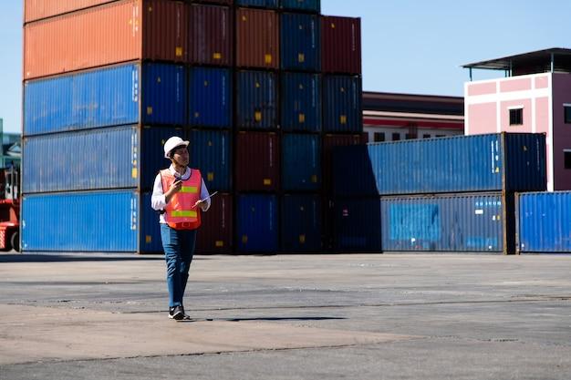 Conceito de seguro marítimo e transportador. controle de contramestre carregando caixa de contêineres no porto de embarque. conceito de logística de negócios de importação e exportação.