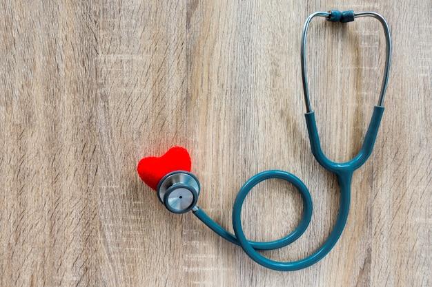 Conceito de seguro médico com estetoscópio na mesa de madeira