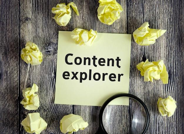 Conceito de seo do explorador de conteúdo - texto em folhas de notas amarelas em uma superfície de madeira escura com folhas amassadas e uma lupa