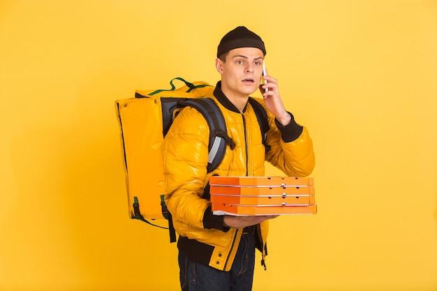 Conceito de serviço de entrega. homem entrega comida e sacolas de compras isoladas na parede amarela