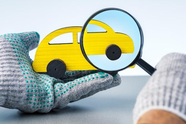 Conceito de serviço do carro. mãos masculinas em luvas com brinquedo de carro para diagnóstico.
