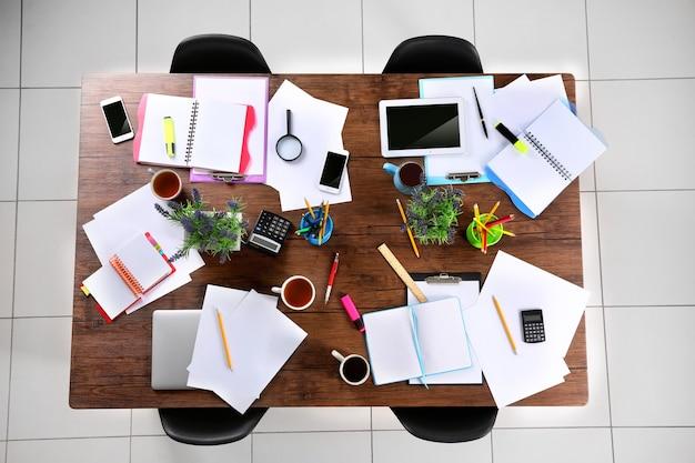 Conceito de sessão. mesa com papéis de laptop tablet e xícaras de chá. vista do topo.