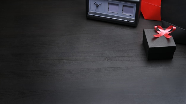 Conceito de sexta-feira negra, caixa de presente preta e fita vermelha em fundo preto.
