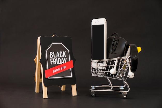 Conceito de sexta feira negra com smartphone no carrinho ao lado do tabuleiro