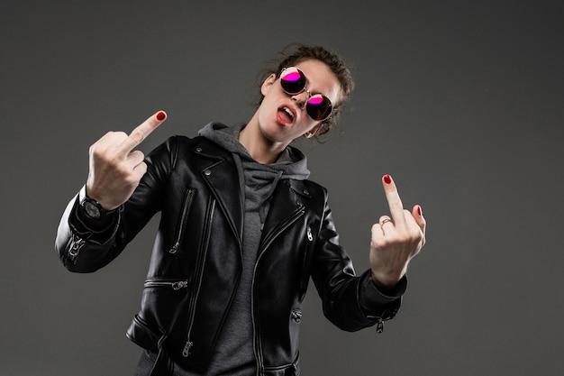 Conceito de sexta-feira negra. garota caucasiana elegante e atraente em uma jaqueta de couro preta e uma camiseta cinza e óculos de sol mostra os dedos do meio sobre um fundo cinza escuro