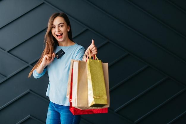 Conceito de sexta-feira negra, mulher alegre com cartão de pagamento e sacolas de compras nas mãos