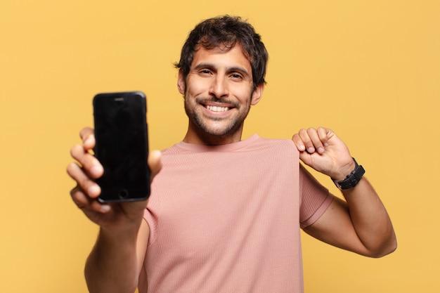 Conceito de smartphone de expressão orgulhosa de jovem indiano bonito