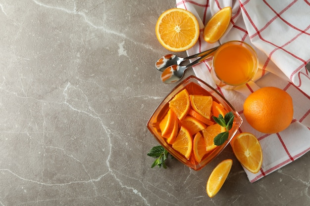Conceito de sobremesa com tigela de geleia de laranja com rodelas de laranja na mesa cinza