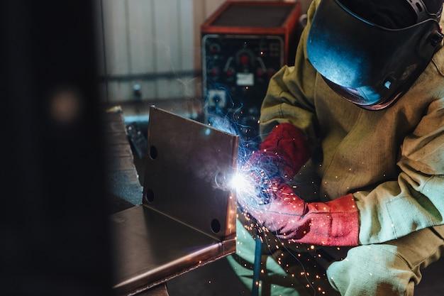 Conceito de soldagem. trabalhador industrial ou soldador usa máscara protetora e luvas ergue aço técnico na fábrica
